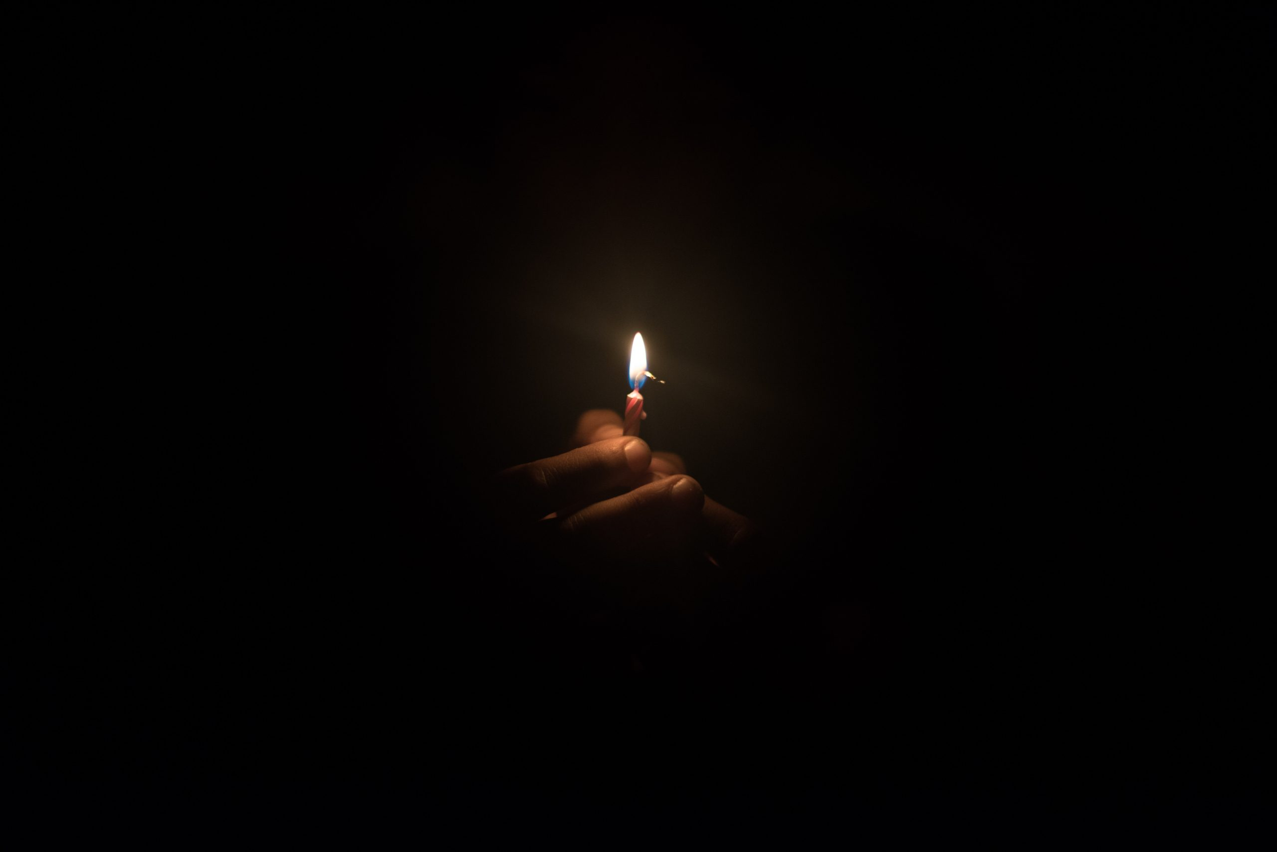 Hand holding burning candle in the dark