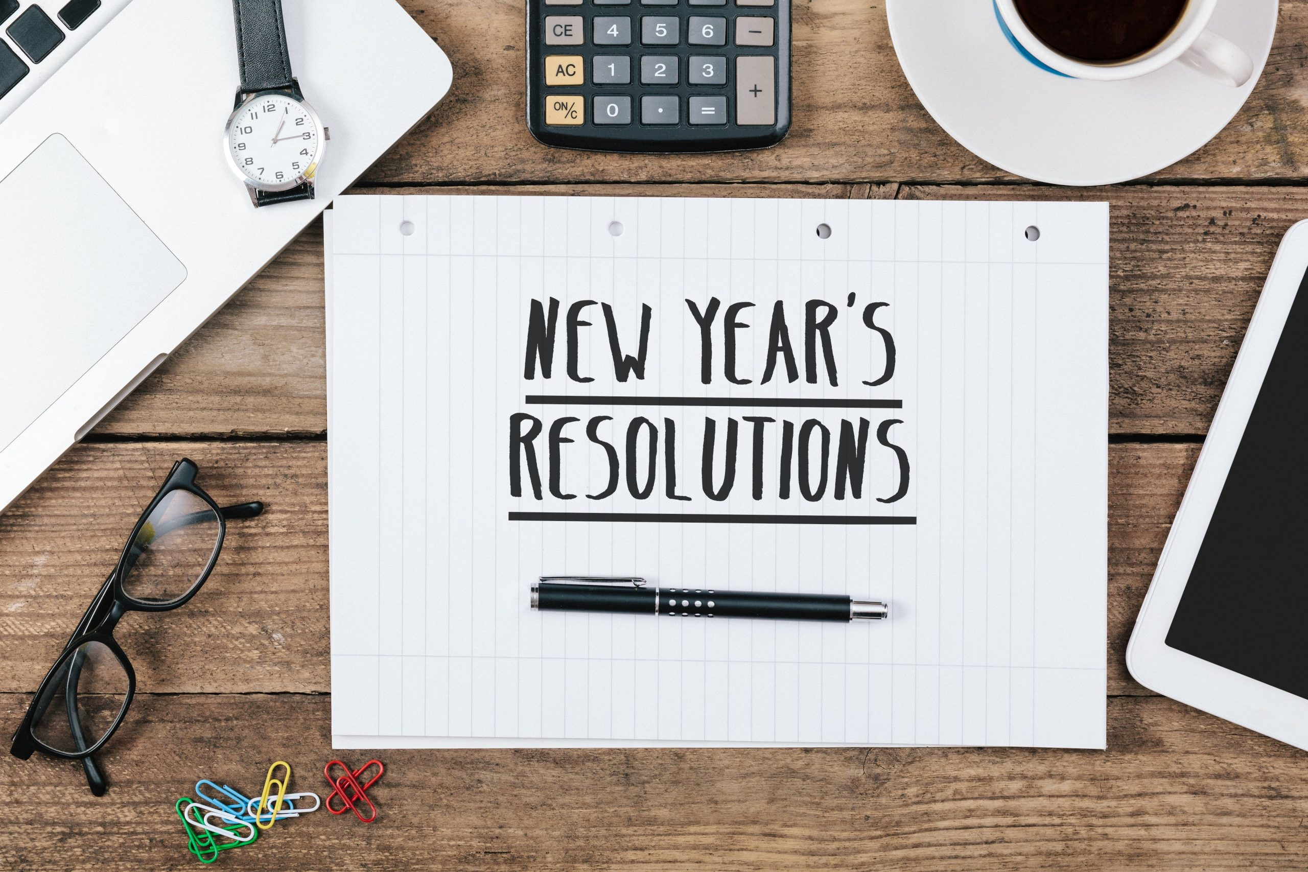 text new years's resolutions on note, Office desk with computer